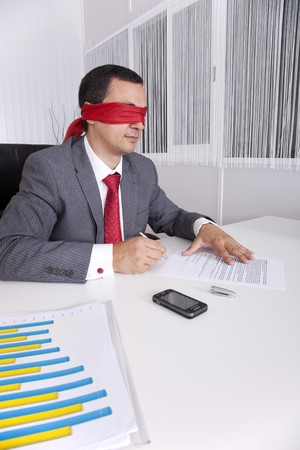 Blindfold businessman at the office working with his laptop Stock Photo - 8171953