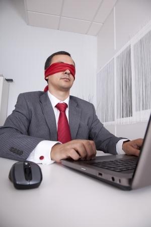 augenbinde: Augenbinde Kaufmann im B�ro arbeiten mit seinem laptop Lizenzfreie Bilder