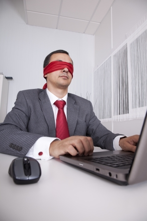 Blindfold businessman at the office working with his laptop photo