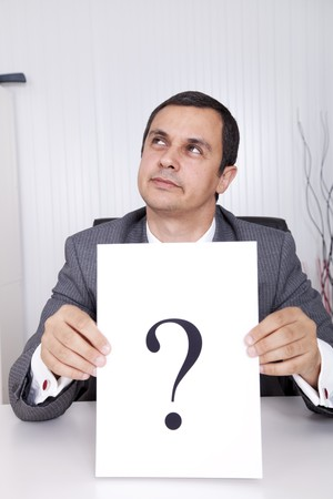 Businessman at the office with a big question Stock Photo - 8172274