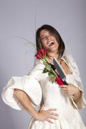 Crazy beautiful bride with a dangerous knife (grey background) Stock Photo - 8174552