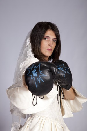 Crazy beautiful bride with boxing gloves (grey background) photo