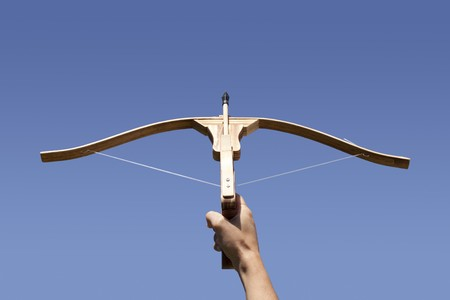 Hand holding a crossbow aiming to the sky photo