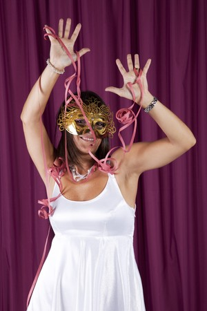 beautiful and sexy woman celebrating with a seductive mask (isolated on black) photo