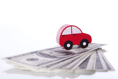 red car over a lot of dollar bills isolated on white  (selective focus) photo