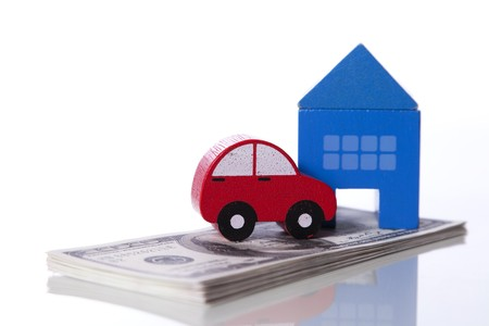 red car and blue house over a lot of dollar bills isolated on white  (selective focus) photo
