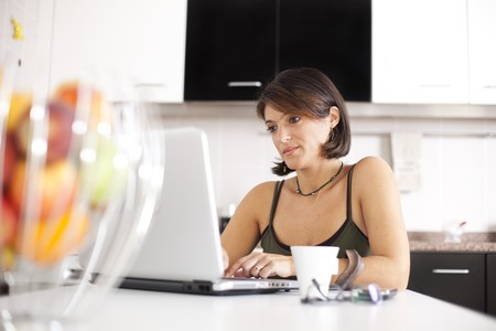 woman working with her laptop while eating her breakfast (selective focus with shallow DOF) photo