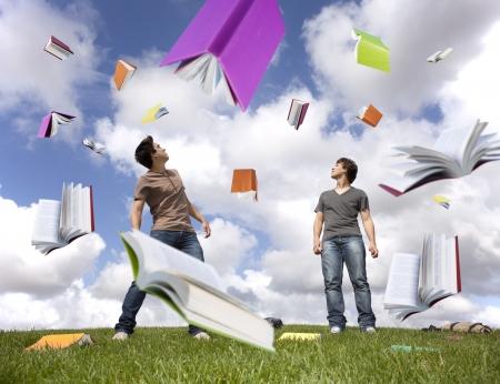 libros volando: Estudiantes de la adolescente fuera de proteger los jefes all� de una lluvia de libros  Foto de archivo