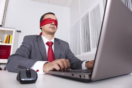paranoia: Blindfold businessman at the office working with his laptop