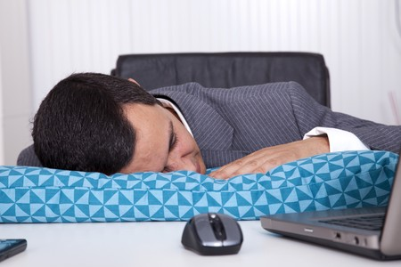 Exhausted businessman sleeping at his office photo