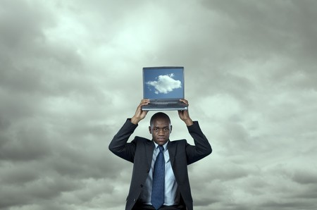 African businessman with a cloud computing solution over a technology storm (cloud computing concept) photo