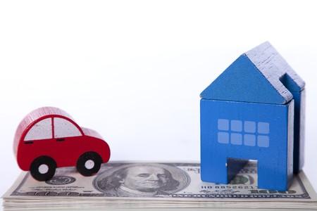 property insurance: auto rojo y la casa azul con un mont�n de billetes de d�lares aislados en blanco (enfoque selectivo) Foto de archivo