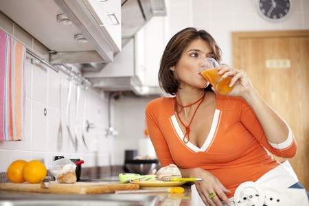 beautiful woman drinking her orange juice and looking natural at her kitchen (selective focus with shallow DOF) photo