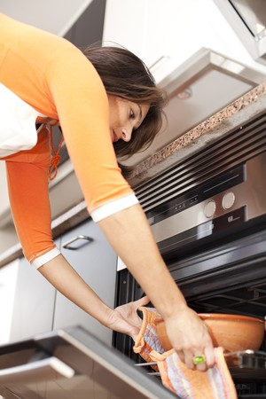 modern woman taken the food out of the kitchen oven Stock Photo - 8171816