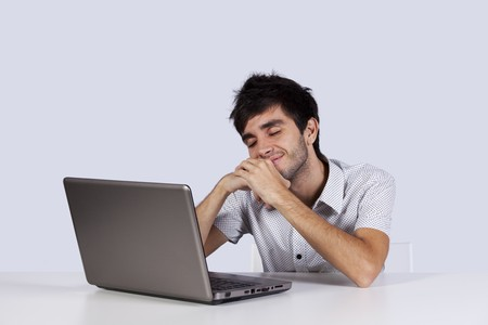 Young man with happy dreams in front of his laptop photo
