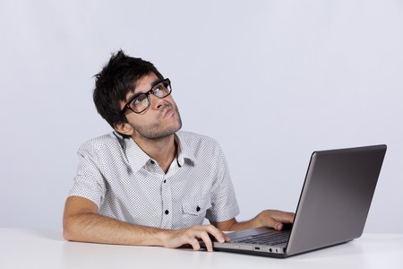 Young man thinking about a solution for a computer problem Stock Photo
