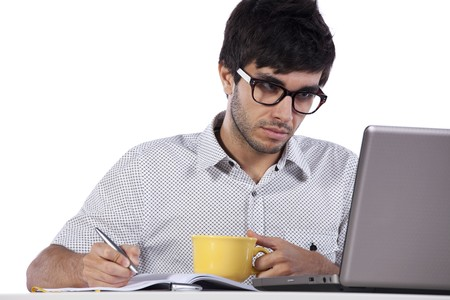 young man writing and looking to his laptop computer photo