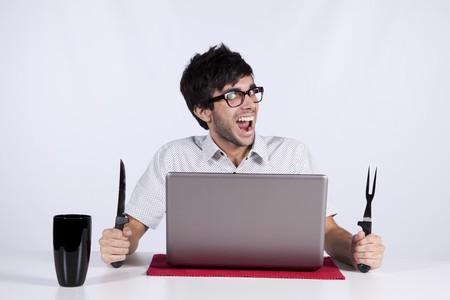 gente loca: Hombres j�venes en mesa comiendo tecnolog�a con una expresi�n de la cara divertida