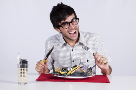out of context: Crazy young man eating technology at his dinner plate