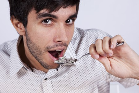 bacon portrait: Man eating money at a plate with a fork and a knife Stock Photo