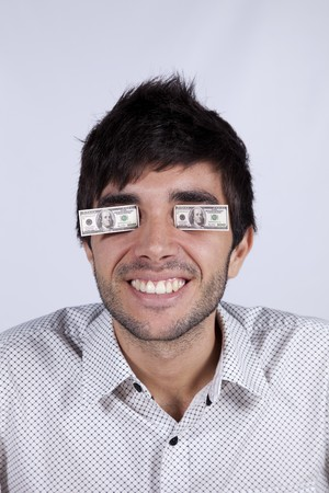 Young man with little dollar bills covering his eyes photo