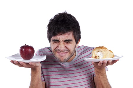unhealthy snack: man thinking what to eat between an apple and a cake (isolated on white)