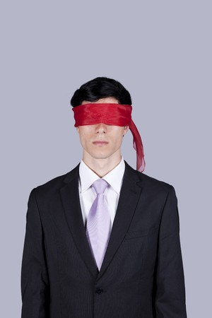 paranoia: Hostage businessman with a red blindfold covering his eyes (isolated on gray) Stock Photo