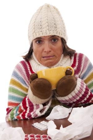 symptom: sad woman with flu symptom holding a mug with a hot drink (isolated on white)