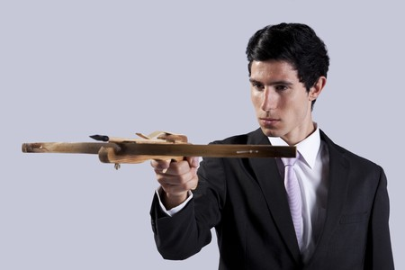 Modern businessman aiming with a crossbow (isolated on gray) Stock Photo - 8171805