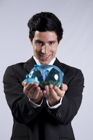 Businessman showing his business profit on a transparent piggybank full of money (isolated on gray) Stock Photo - 8174766