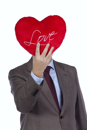 Businessman holding a red pillow with a heart shape in front of his head (isolated on white) Stock Photo - 8652347