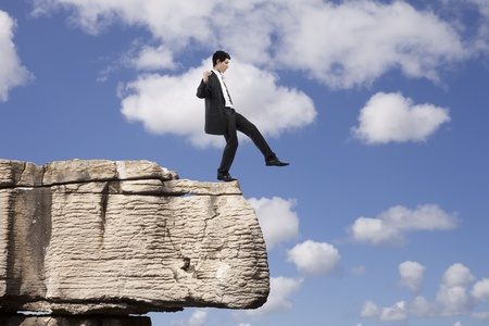 strategy decisions: Businessman making a danger and step falling from a rock