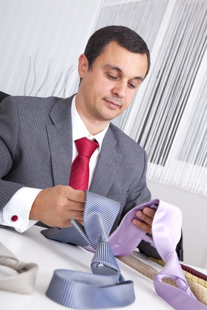 mature businessman looking to a lot of neckties, thinking what to choose Stock Photo - 8652744