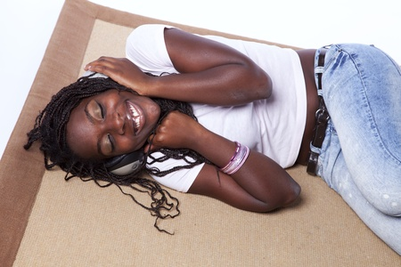 young african woman listening to music (isolated on white) photo