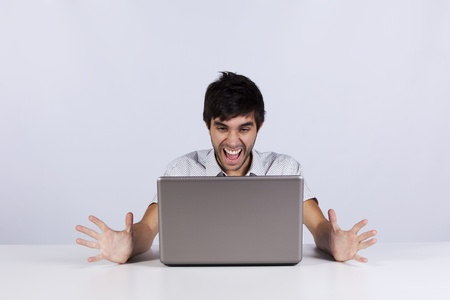 Young man looking to something terrible and screaming to his laptop photo