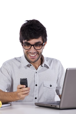 Young modern businessman using the phone and working with his laptop Stock Photo - 8652656