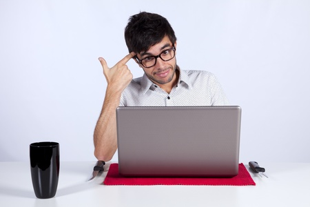Young men at dinner table eating technology with a suicide gesture while working with his laptop photo