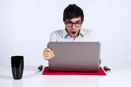 freak out: young man shocked with something he see on his laptop computer