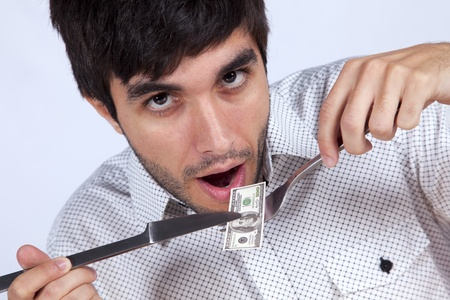 bacon portrait: Man eating money with a fork and a knife Stock Photo