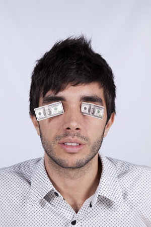 Young man with little dollar bills covering his eyes Stock Photo - 8652647