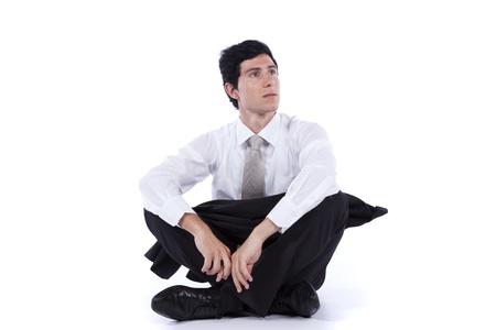 persona sentada: Empresario joven y moderno relajante en el piso con las piernas cruzadas (aislado en blanco)
