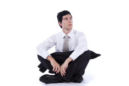 sitting floor: Young and modern businessman relaxing on the floor with his legs crossed (isolated on white)