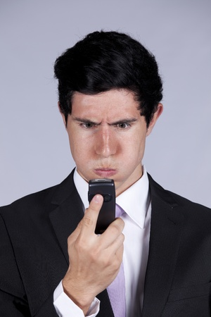 Businessman with a angry face expression looking to his mobile phone (isolated on gray) photo