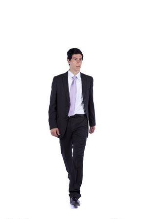 person walking: Businessman walking and looking away isolated on white (some motion blur)