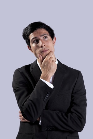 Young businessman thinking and looking up (isolated on gray) Stock Photo - 8652412