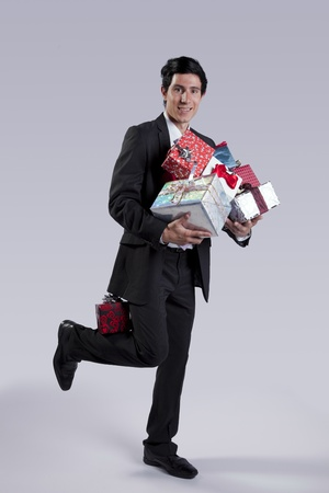 christmas bonus: Businessman with a lot of gift packages (isolated on gray)