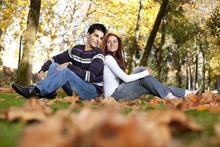 Love and affection between a young couple at the park in autumn season (selective focus with shallow DOF) Stock Photo - 8652712