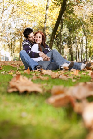 Love and affection between a young couple at the park in autumn season (selective focus with shallow DOF) Stock Photo - 8651778