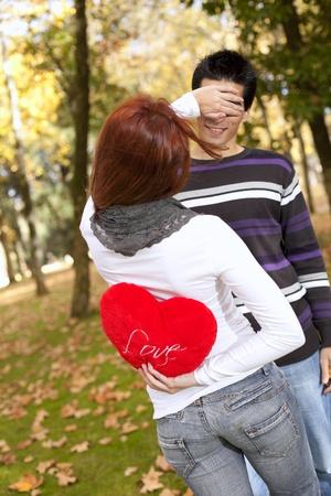 donna innamorata: donna che coprono gli occhi al suo fidanzato detiene un cuore rosso dietro di lei indietro (messa a fuoco differenziale con shallow DOF)