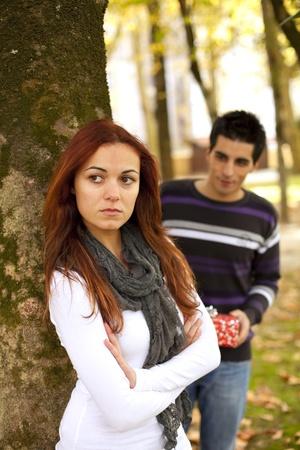 angry couple: Pareja con el problema de la relaci�n, ella est� enojada con �l, pero tiene un presente para hacer su feliz (enfoque selectivo con poca profundidad DOF) Foto de archivo